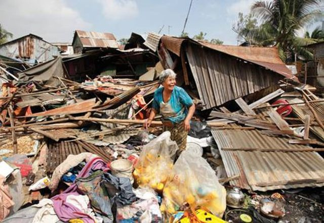An elderly woman cries amidst the remains of her home in Cambodia
